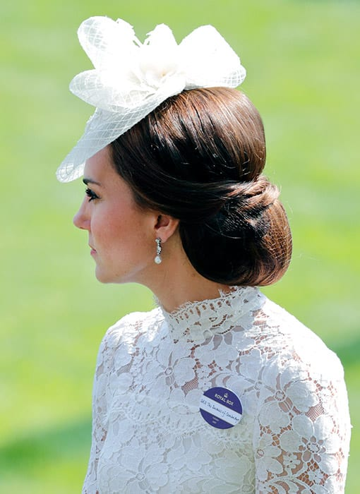 Catherine, Duchess of Cambridge poses in white dress and hair bun