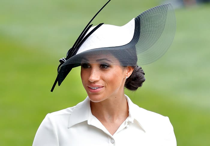 Meghan Markle with a black hat and bun hairstyle