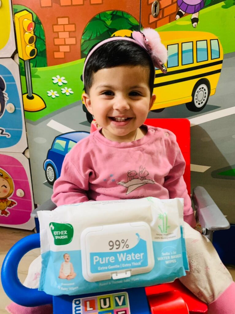 Best Baby Wipes India - Infant wears a pink t-shirt and has Mother Sparsh wipes  in her hand